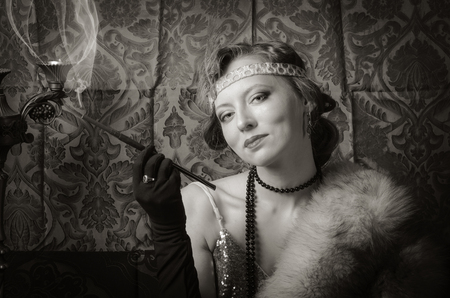 Girl in an evening dress with a cigarette mouthpiece. Studio portrait in retro style, toned in sepia