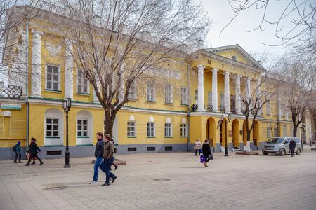 Orenburg Local History Museum. Orenburg, Russia - April, 2, 2019: Sovetskaya Street. Passers-by against the background of the facade of an old building Editöryel