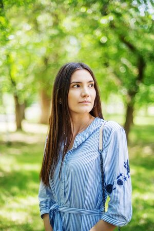 A girl of Asian appearance in a city park. Summer portrait of young Tatar on a background of green foliage