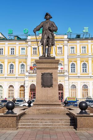 Monument to Rychkov, Peter Ivanovich. Orenburg, Russia - May, 8, 2019: Rychkov Monument on the background of the facade of the building of the old railway station
