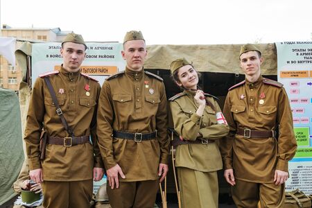 People in the uniform of military medics, against the background of the layout of the military field hospital. Orenburg, Russia - May 9, 2019: Celebration of Victory Day Sajtókép
