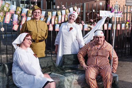 Wounded with a bandaged head, and military doctors. Orenburg, Russia - May 9, 2019: Celebration of Victory Day Sajtókép