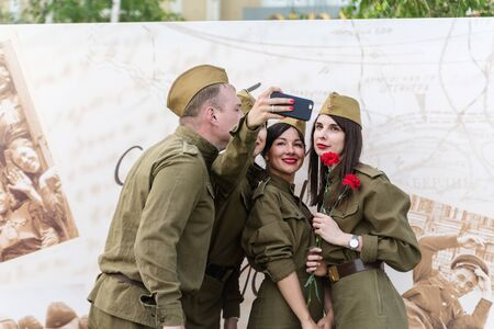 Young people in military uniform of the Great Patriotic War, make selfie on your smartphone. Orenburg, Russia - May 9, 2019: Celebration of Victory Day