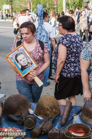 Participants in the action Immortal Regiment, at a street exhibition of artifacts during the Second World War. Orenburg, Russia - May 9, 2019: Celebration of Victory Day Sajtókép