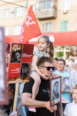 A young father with a daughter on his shoulders, participants in the action Immortal Regiment. Orenburg, Russia - May 9, 2019: Celebration of Victory Day Sajtókép