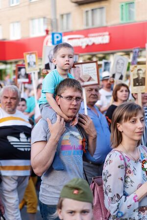A young father with a son on his shoulders, participants in the action Immortal Regiment. Orenburg, Russia - May 9, 2019: Celebration of Victory Day Sajtókép