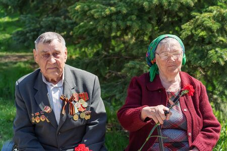 An elderly couple of labor veterans, on a holiday. Orenburg, Russia - May 9, 2019: Celebration of Victory Day