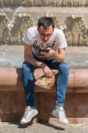 A young man looks at the screen of a smartphone, sitting on the edge of a fountain. Orenburg, Russia - May 9, 2019: Street. City life Sajtókép