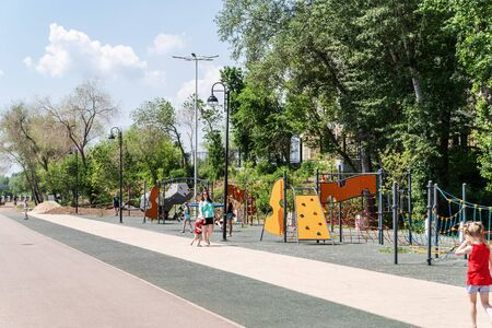 Orenburg, Russia - June, 1, 2019: Embankment of the Urals. The plot of the city embankment with a playground and strolling citizens Sajtókép