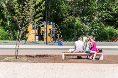Orenburg, Russia - June, 1, 2019: Embankment of the Urals. Summer. The plot of the city embankment with a playground. Family sitting on a bench