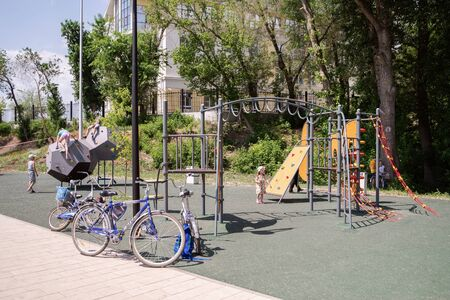Orenburg, Russia - June, 1, 2019: Embankment of the Urals. Summer. Bicycles parked near the playground, with children playing Sajtókép