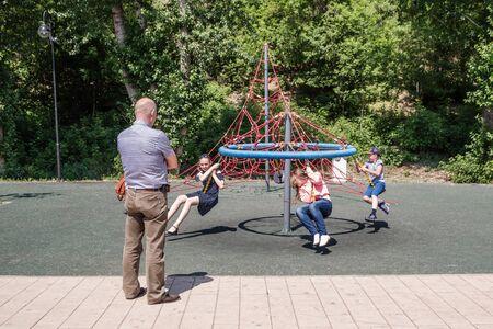 Orenburg, Russia - June, 1, 2019: Embankment of the Urals. Summer. Elderly man watching children playing on the playground