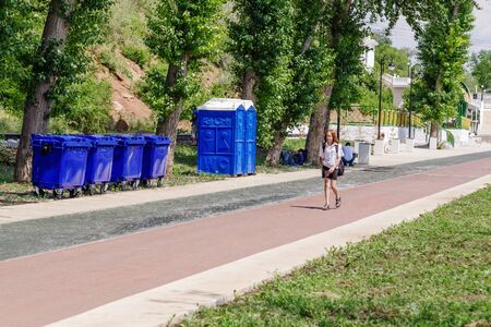Orenburg, Russia - June, 1, 2019: Embankment of the Urals. Summer. A girl walking along a path past garbage cans, dry closets and migrants resting in the shade of trees Sajtókép