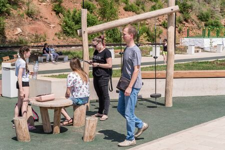 Orenburg, Russia - June, 1, 2019: Embankment of the Urals. Summer. Citizens rest on a wooden playground