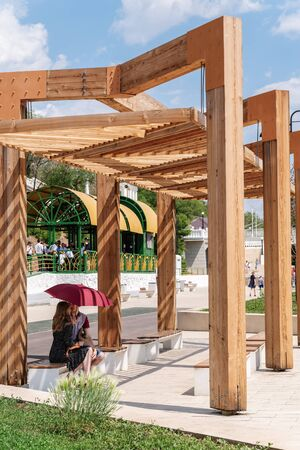 Orenburg, Russia - June, 1, 2019: Embankment of the Urals. Summer. A young couple is sitting in a wooden gazebo with an umbrella