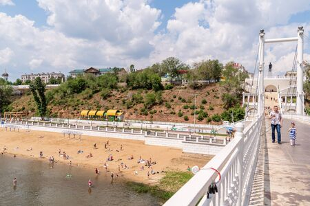 Orenburg, Russia - June, 1, 2019: Dad with a little daughter eating ice cream on a walk. View of the beach and embankment of the Ural River from the pedestrian bridge