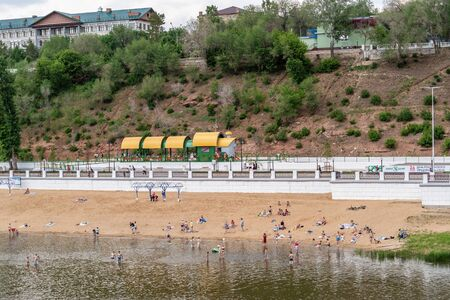 Orenburg, Russia - June, 1, 2019: People swim and sunbathe on the river beach. View of the beach and the embankment of the Ural River