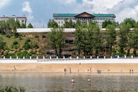 Orenburg, Russia - June, 1, 2019: People swimming in the Ural river and relaxing on the beach. Central beach and promenade