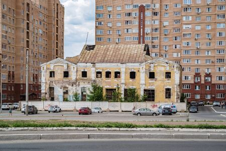 Orenburg, Russia - June, 1, 2019: Old abandoned building of the Distillery among the new buildings. Riverside Housing Estate