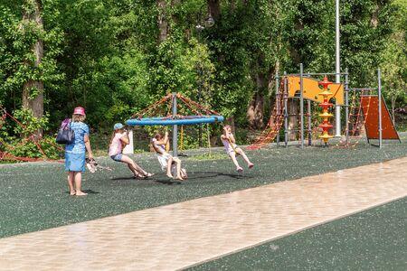 Orenburg, Russia - June, 1, 2019: Embankment of the Urals. Summer. Woman watching children playing on the playground