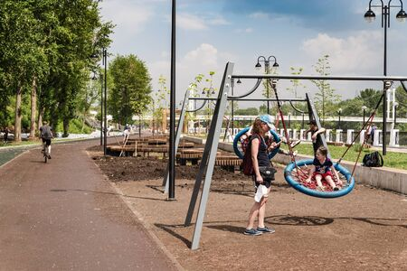 Orenburg, Russia - June, 1, 2019: Young mother with children at the playground. Section of the embankment of the Ural River Sajtókép