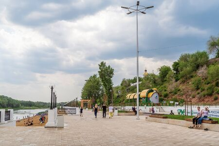 Orenburg, Russia - June, 1, 2019: City promenade and beach, people having a rest and walking. After the rain