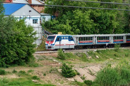 Orenburg, Russia - June, 1, 2019: Orenburg Childrens Railway. A locomotive with passenger cars moves along the banks of the Ural River Sajtókép