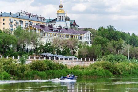 Orenburg, Russia - June, 1, 2019: Motor boat on the Ural river. City landscape with the embankment and riverbanks Sajtókép