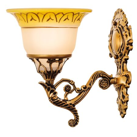 Sconce with yellow glass shade with ornament, made of golden metal. Antique style wall lamp isolated on white background 写真素材