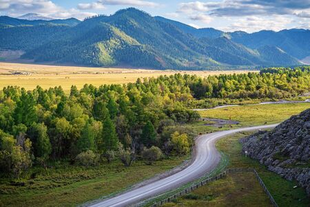Rural mountain landscape in the fall. Russia, mountain Altai, Ongudaysky district, the road and the Karakol river valley, near the village of Bichiktu-Boom