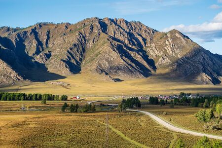 Rural mountain landscape with a road. Russia, mountain Altai, Ongudaysky district, the village of Karakol