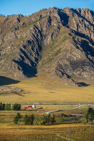 Rural mountain landscape with a road. Russia, mountain Altai, Ongudaysky district, near the village of Karakol