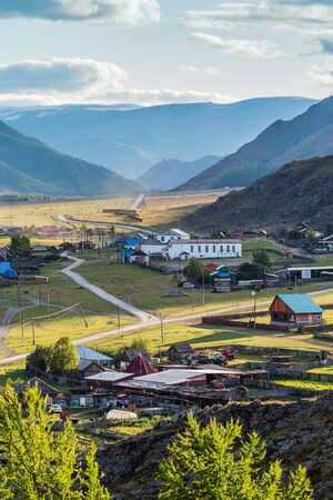 Rural autumn mountain landscape with a village. Russia, mountain Altai, Ongudaysky district, the village of Bichiktu-Boom Stock Photo