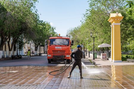 Orenburg, Russia - June, 14, 2019: Watering machine on a city street. Worker washes Soviet street in the morning
