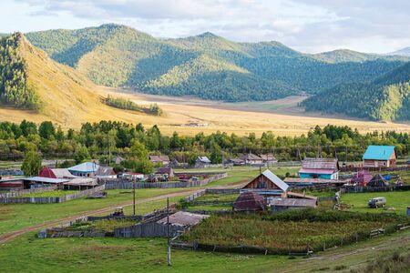 Dorf in einem Bergtal am Abend. Russland, Berg Altai, Bezirk Ongudaysky, das Dorf Bichiktu-Boom Standard-Bild