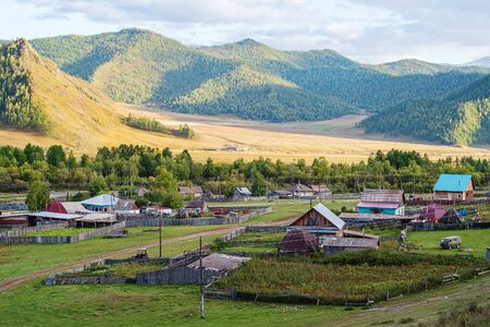 Village in a mountain valley in the evening. Russia, mountain Altai, Ongudaysky district, the village of Bichiktu-Boom