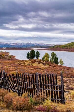 Autumn mountain landscape, old wooden fence on the shore of Uzunkel lake. Ulagansky District, Altai Republic, Russia 版權商用圖片