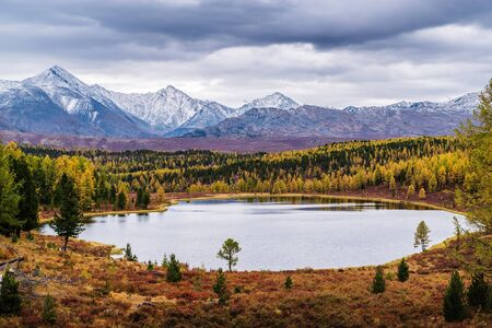 View of the Kidelu Lake and the snow-capped peaks of the Kurai ridge on the horizon. Autumn mountain landscape. Ulagansky District, Altai Republic, Russia