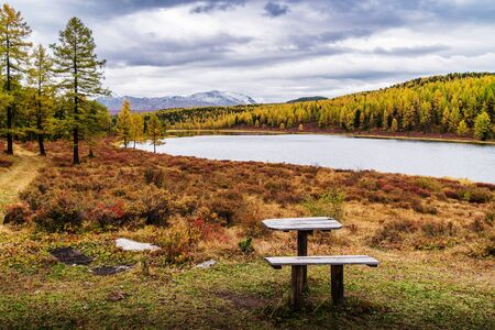 The shore of Lake Kidelu and the snowy peaks of the Kurai ridge on the horizon. Autumn mountain landscape. Ulagansky District, Altai Republic, Russia