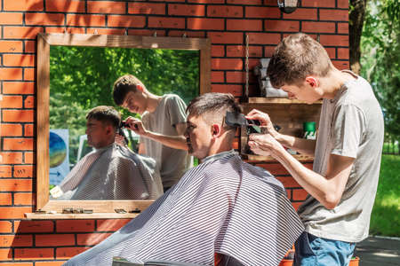 Orenburg, Russia - July, 20, 2019: Hairdresser cuts a man in an open air salon. FORMA MARKET - a city festival for the promotion of handmade designers, artisans and their projects with the aim of engaging in the business environment