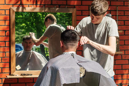 Orenburg, Russia - July, 20, 2019: Men's haircut in an open air salon. FORMA MARKET - a city festival for the promotion of handmade designers, artisans and their projects with the aim of engaging in the business environment