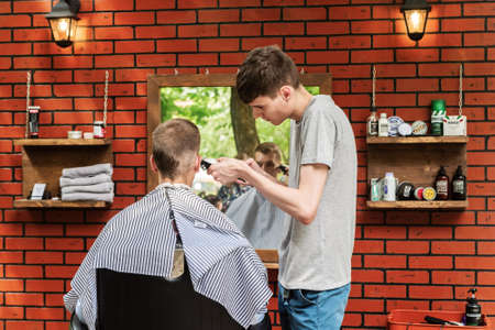 Orenburg, Russia - July, 20, 2019: Men's haircut at the hairdresser in the open air. FORMA MARKET - a city festival for the promotion of handmade designers, artisans and their projects with the aim of engaging in the business environment