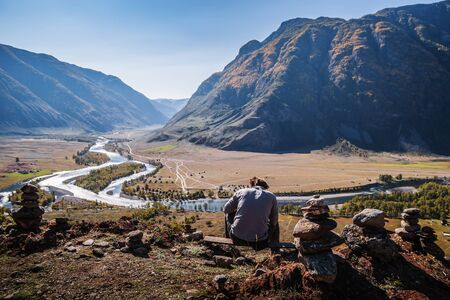 A man sitting on top with a view of the valley of a mountain river. Russia, Altai Republic, Ulagansky District, Chulyshman River, Akkrum tract 版權商用圖片