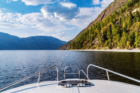 The nose of a motor boat sailing on a mountain lake. View from the cockpit right on course. Fall. Russia, Altai Republic, Lake Teletskoye