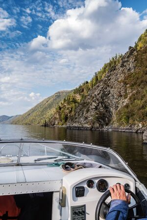 Steering wheel and dashboard of a pleasure boat. The view from the cab. Russia, Altai Republic, Lake Teletskoye