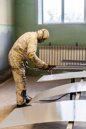 The painter in protective overalls works in the paint shop. Photo taken at the factory floor