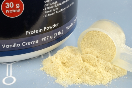 Protein Powder with Measuring Spoop on a Blue Background