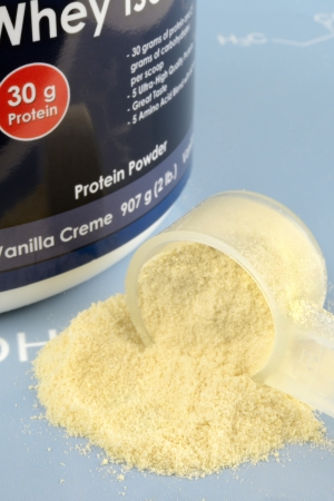 Protein powder with measuring spoop on blue background