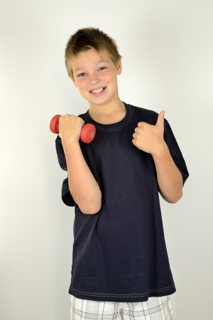 9 year old: 9 year old boy is doing workout with a dumbbell Stock Photo