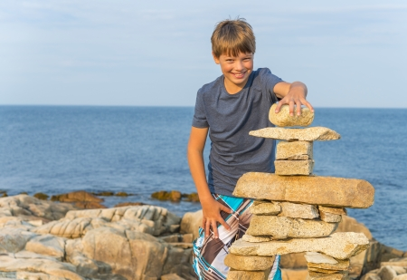 inukshuk: Boy building inukshuk on the rocky beach  Duncan Cove, Nova Scotia, Canada